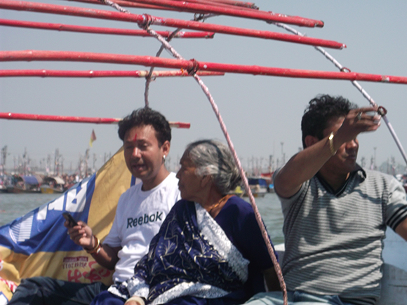 Modern youth with elderly lady participating in Kumbh Mela