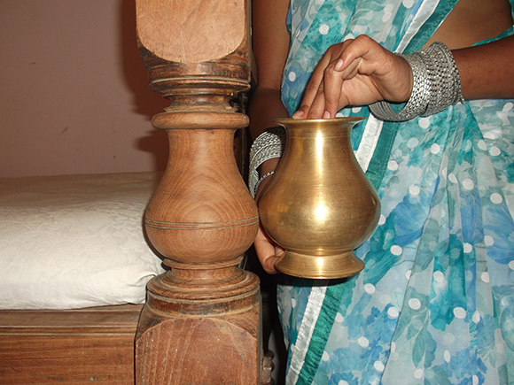 Close-up view of Identical Design on the Wood Cot and the Brass Drinking Pot.