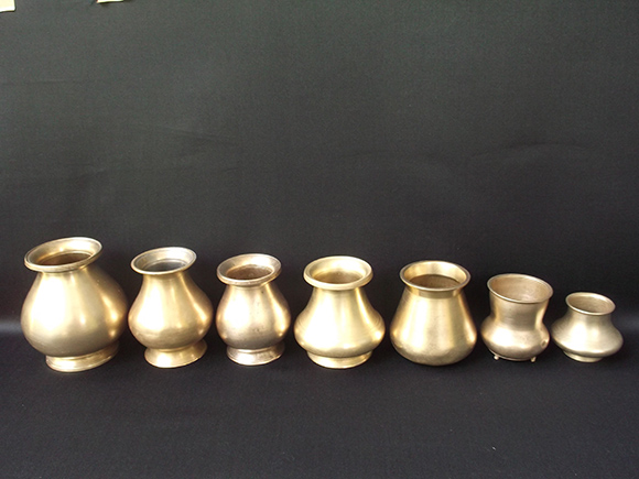 Antique Brass Drinking Pots Arranged size-wise in a Row.