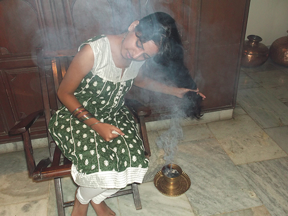 Drying up the sides of the hair with perfumed sambrani smoke.