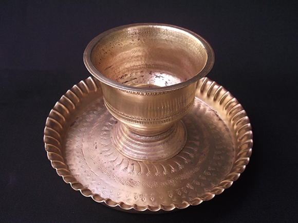 Brass pot is always carried on the plate for practical reasons.