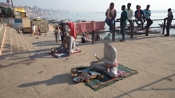 Two naked Naga sect Sadhus doing prayers with Kamandalam in front of them.
