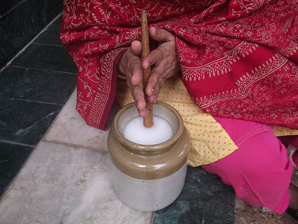 Lady churning the lassi in a porcelain pot with wooden churner. Close up view.