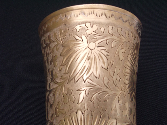 Antique Punjabi brass lassi tumbler glass – Intricate carved design on the body of the glass. Close-up view.