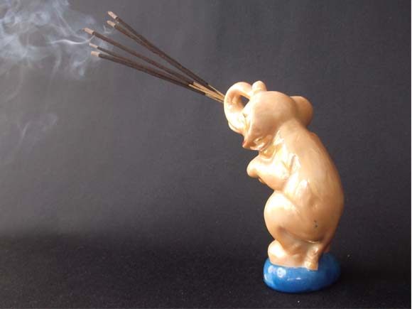 Rear view of the elephant holding incense sticks with curling smoke