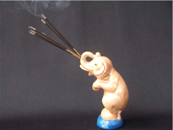 Elephant holding burning incense sticks