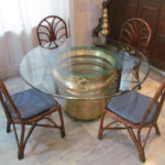 Huge antiques brass gangalam that  serves as a base of the dining table with a glass top