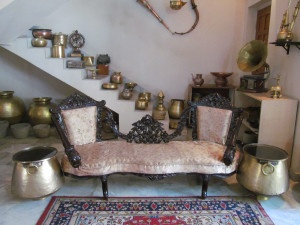 A reconditioned antique Portuguese protocol sofa matched with two old brass vessels repurposed as peg tables with glass top