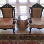 Two old Portuguese  chairs restored .One old brass vessel with glass top positioned as tea table, Two huge brass Gangalams serve as curtain holders