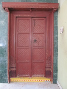 Antique main door with carved frame,projected canopy,brass handle, locking chain and turmeric yellow threshold