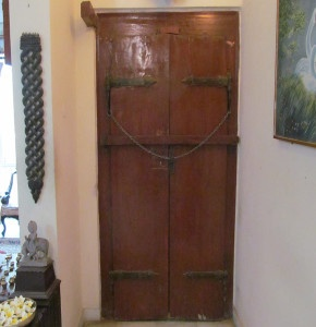 Back side view of the door with wooden plank across the door and heavy chain