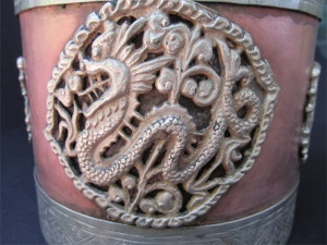 The embellishment of single dragon surrounded by intricate design forming a round shape