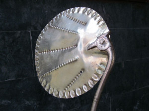 Hand –held brass fan showing the design joining the leaves and boarder design around the edge of the fan