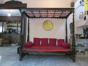 An intricately carved four post antique cot with canopy can be re-purposed as a divan with arrangement of bolsters and pillows