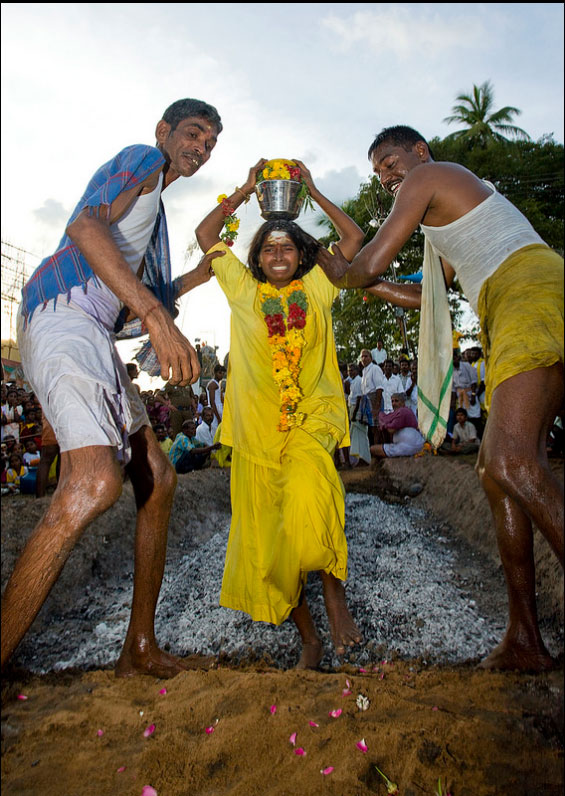 Lady devotee wearing yellow sari, holding the pot (kalasam) on head and wearing a garland of marigold flowers being escorted by volunteers after completing fire walking ceremony.