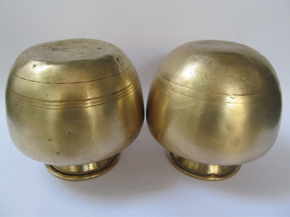 Two identical brass pots one with depression at the bottom and the other with the rounded bottom shape.