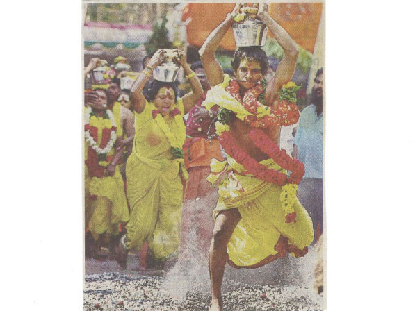 Devotees doing Fire walking with flower decked kalasam on their head wearing yellow cloths, garland around the neck. with spiritual fervor.